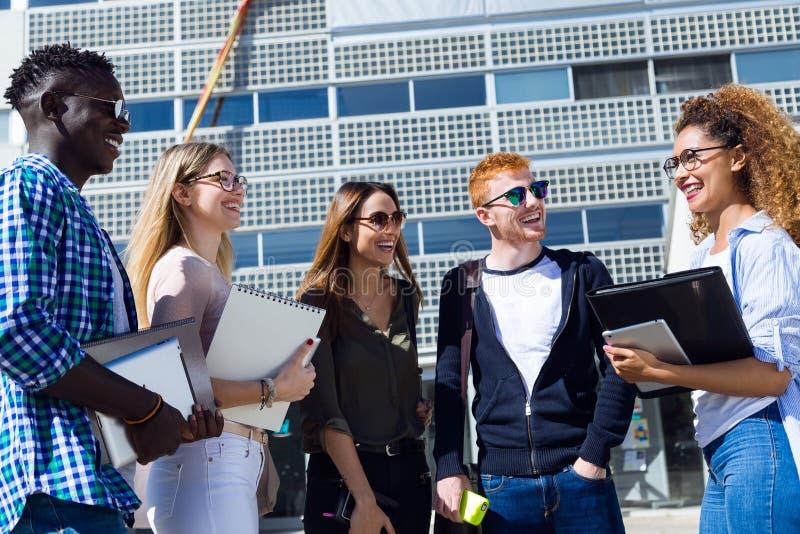 Grupp av lyckliga unga studenter som talar i ett universitet royaltyfria foton