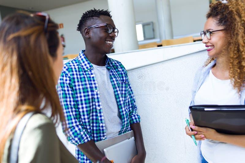 Grupp av lyckliga unga studenter som talar i ett universitet royaltyfri fotografi