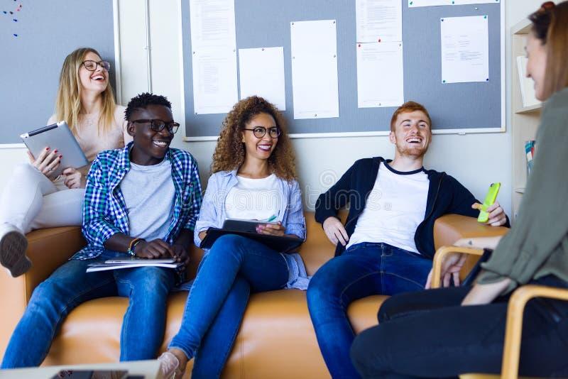 Grupp av lyckliga unga studenter som talar i ett universitet arkivbild