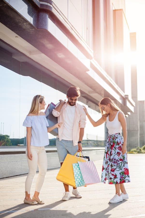 Grupp av lyckliga unga vänner som går tillbaka från shopping arkivbild