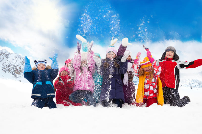 Grupp av lyckliga ungar som kastar snö royaltyfri foto