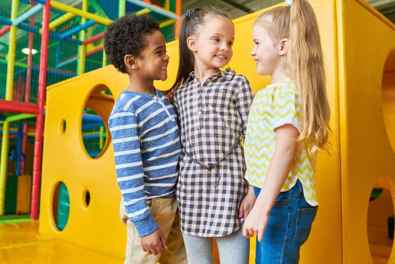 Grupp av lyckliga ungar som poserar i lekområde royaltyfria bilder
