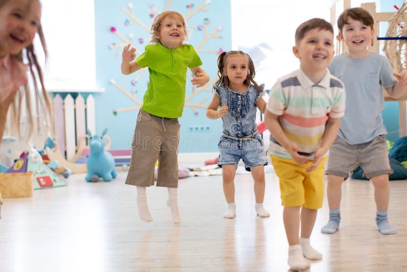 Grupp av lyckliga ungar som spelar och hoppar royaltyfri bild