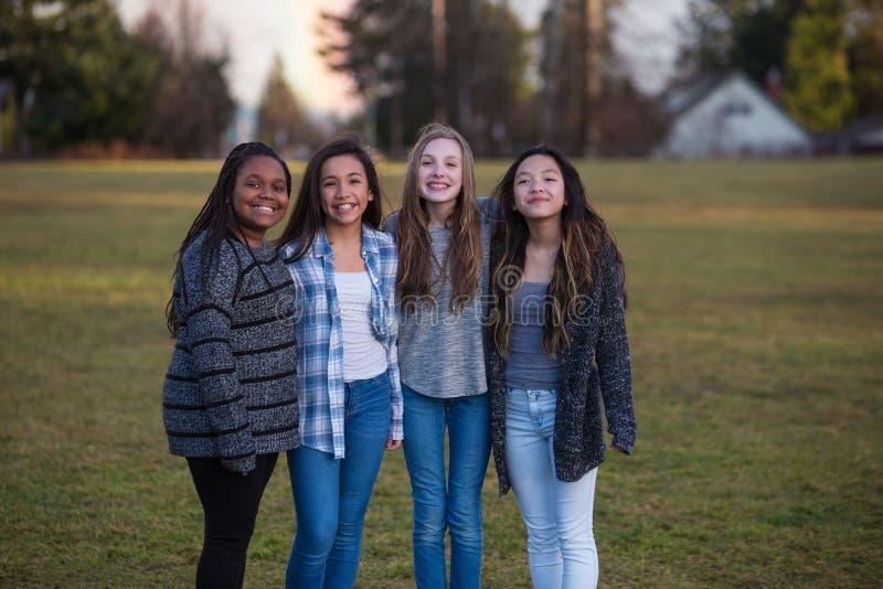 Grupp av lyckliga ungar som tillsammans utanför står arkivbilder