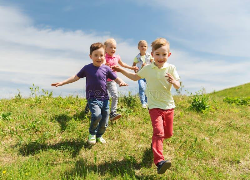 Grupp av lyckliga ungar som utomhus kör royaltyfria bilder