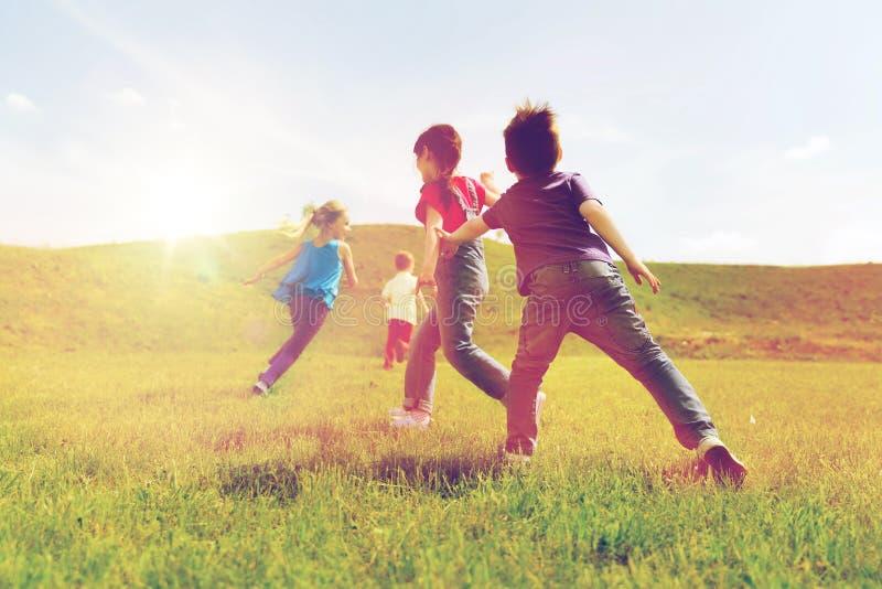 Grupp av lyckliga ungar som utomhus kör royaltyfri bild