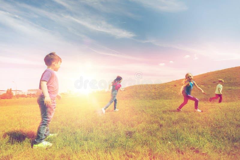 Grupp av lyckliga ungar som utomhus kör arkivbild