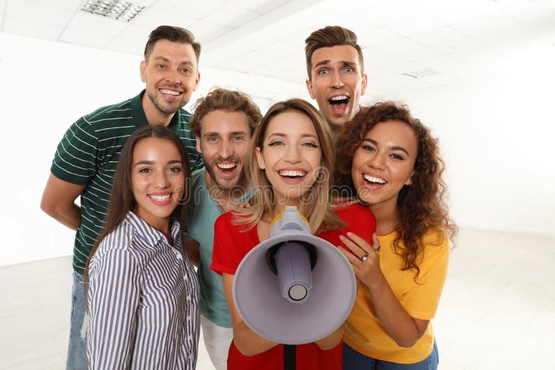 Grupp av lyckliga ungdomarmed megafonen royaltyfria bilder