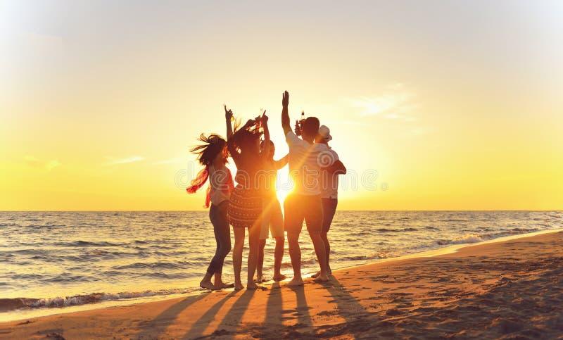 Grupp av lyckliga ungdomarsom dansar på stranden på härlig sommarsolnedgång fotografering för bildbyråer