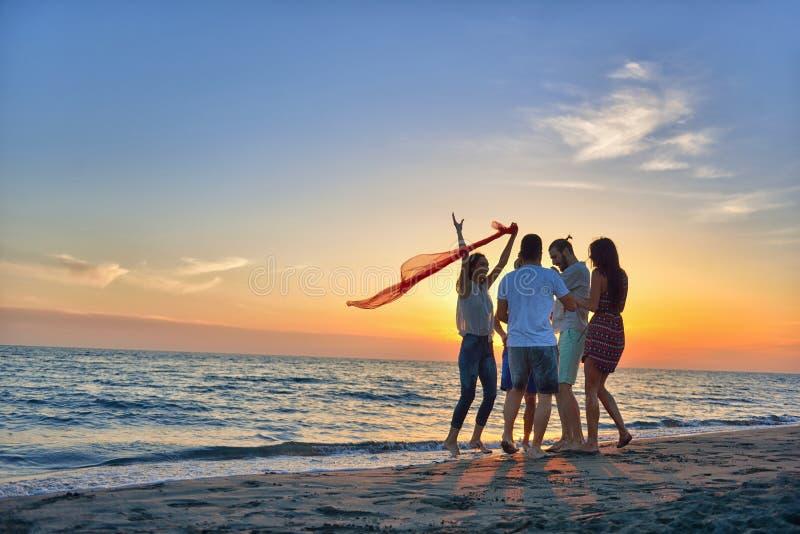 Grupp av lyckliga ungdomarsom dansar på stranden på härlig sommarsolnedgång arkivfoton