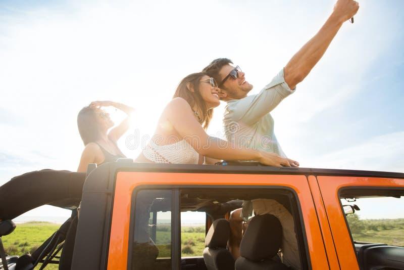 Grupp av lyckliga ungdomarsom tar selfie med smartphonen arkivfoto
