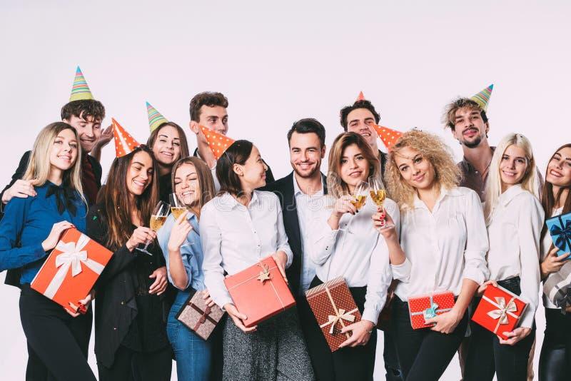 Grupp av lyckliga ungdomarsom tillsammans firar och har gyckel över vit bakgrund royaltyfri foto