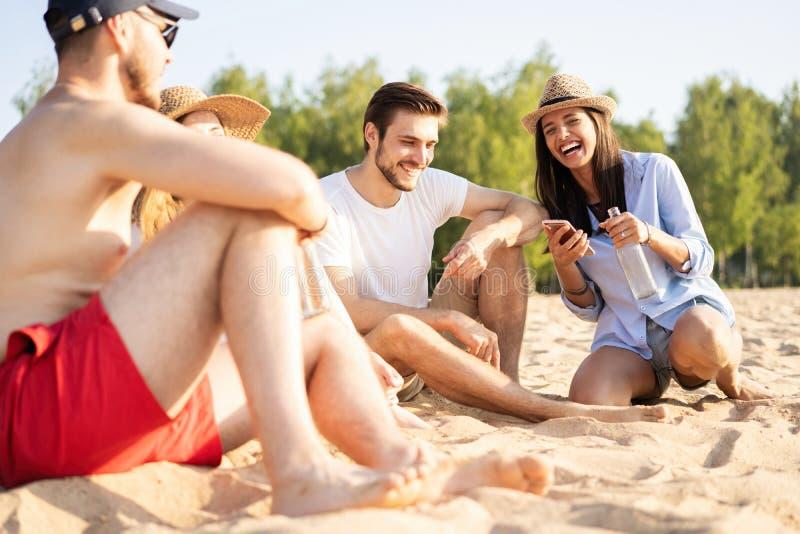 Grupp av lyckliga ungdomarsom tillsammans sitter p? stranden som talar och dricker ?l fotografering för bildbyråer