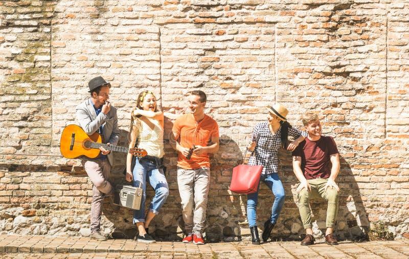 Grupp av lyckliga upphetsade vänner som har roligt utomhus- bifall med arkivfoton