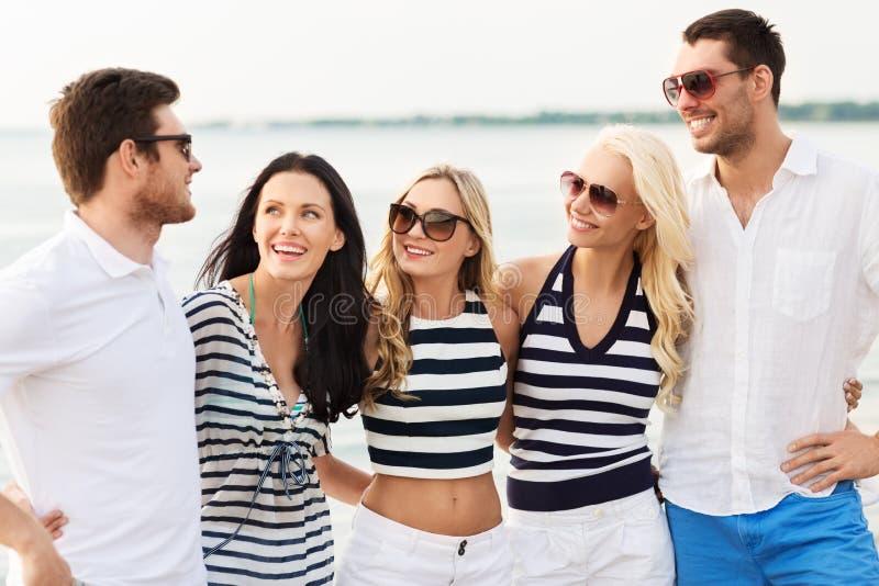 Grupp av lyckliga vänner i randig kläder på stranden royaltyfria foton