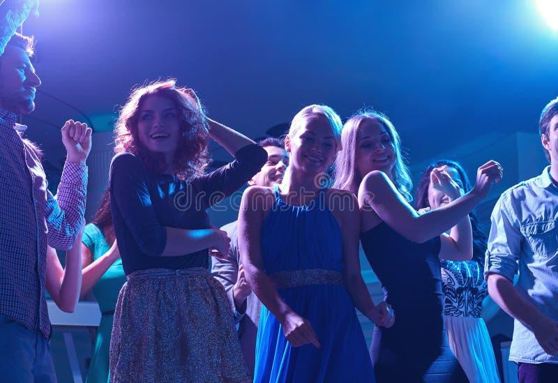 Grupp av lyckliga vänner som dansar i nattklubb fotografering för bildbyråer