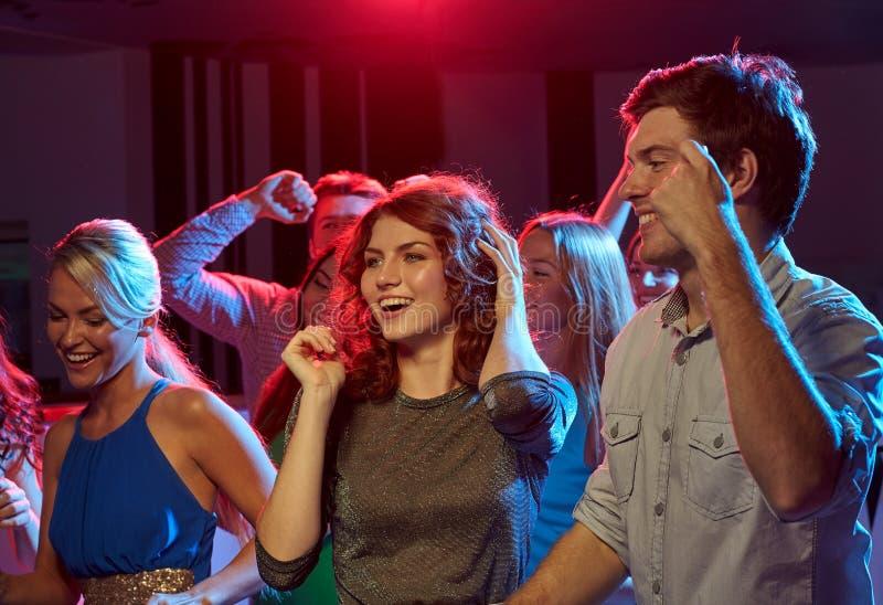 Grupp av lyckliga vänner som dansar i nattklubb royaltyfria bilder