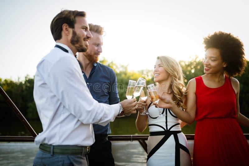 Grupp av lyckliga vänner som festar och rostar drinkar arkivfoton
