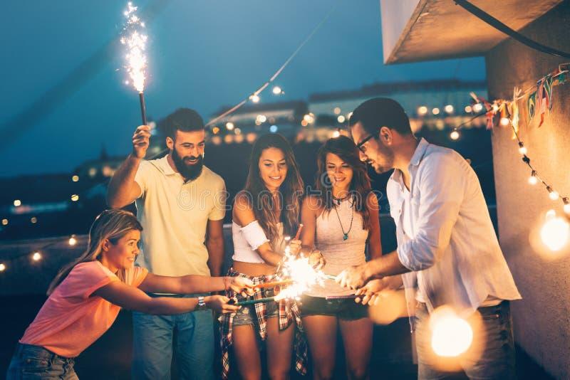 Grupp av lyckliga vänner som firar på taket royaltyfri fotografi
