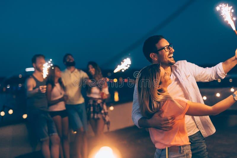 Grupp av lyckliga vänner som firar på taket arkivfoton