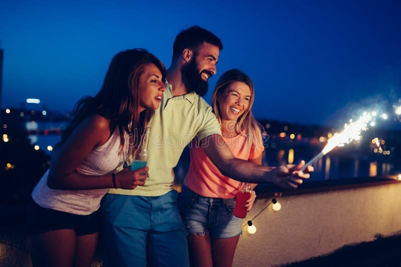 Grupp av lyckliga vänner som firar på taket royaltyfria bilder