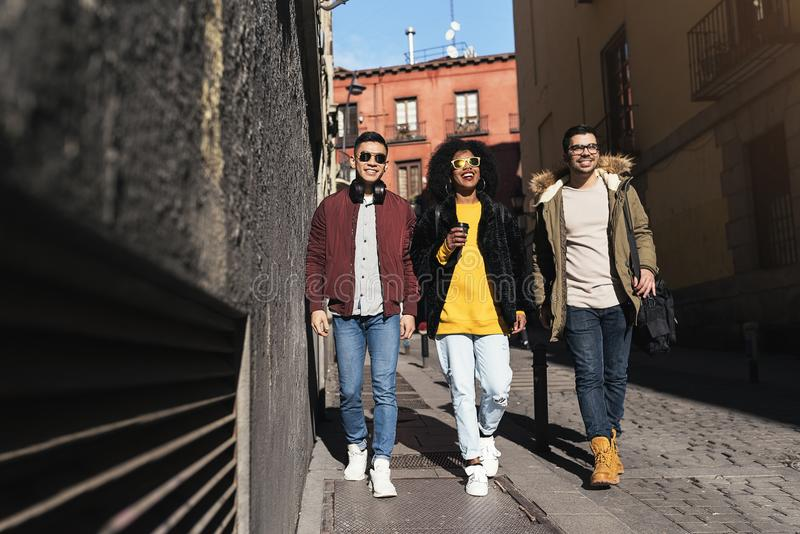 Grupp av lyckliga vänner som går i gatan arkivfoton