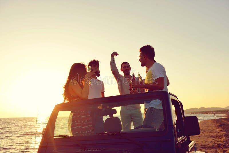 Grupp av lyckliga vänner som gör partiet i bil- ungdomarsom har gyckel som dricker champagne arkivbild
