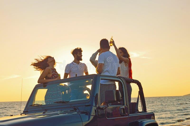 Grupp av lyckliga vänner som gör partiet i bil- ungdomarsom har gyckel som dricker champagne arkivfoton