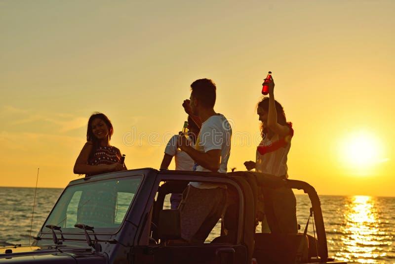 Grupp av lyckliga vänner som gör partiet i bil- ungdomarsom har gyckel som dricker champagne royaltyfria bilder