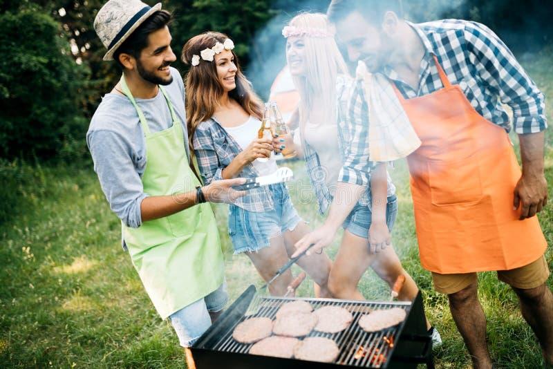 Grupp av lyckliga vänner som har den utomhus- grillfesten som tillsammans skrattar royaltyfri bild