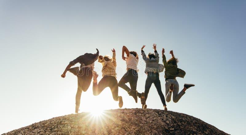 Grupp av lyckliga vänner som har gyckel på bergöverkant royaltyfria bilder