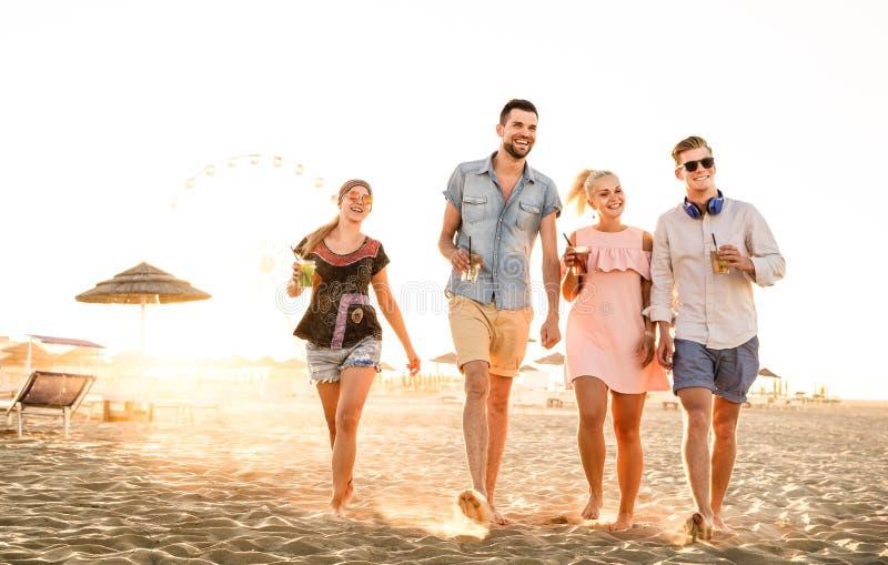 Grupp av lyckliga vänner som har gyckel på sjösidasolnedgången - sommarsemestrar och kamratskapbegrepp med ungdomarmillennials arkivbilder