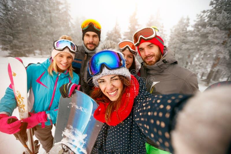 Grupp av lyckliga vänner som har rolig snowboarders- och skidåkareframställning royaltyfri foto