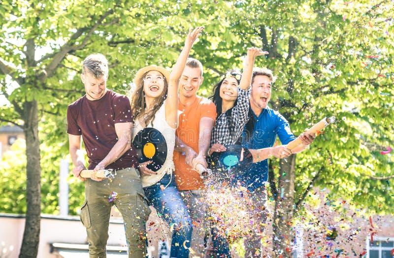 Grupp av lyckliga vänner som har roligt utomhus- bifall med konfettier royaltyfri bild