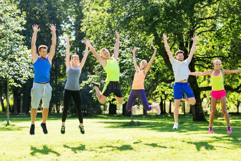 Grupp av lyckliga vänner som hoppar högt på parken arkivfoto
