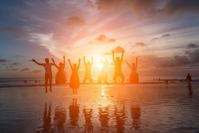 Grupp av lyckliga vänner som hoppar på stranden mot solnedgång arkivbild