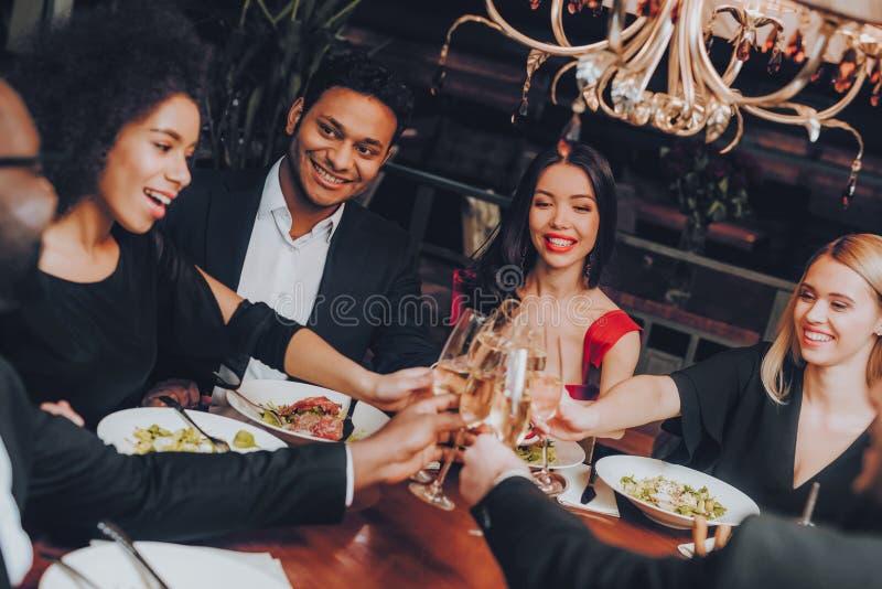 Grupp av lyckliga vänner som möter och har matställen royaltyfria foton