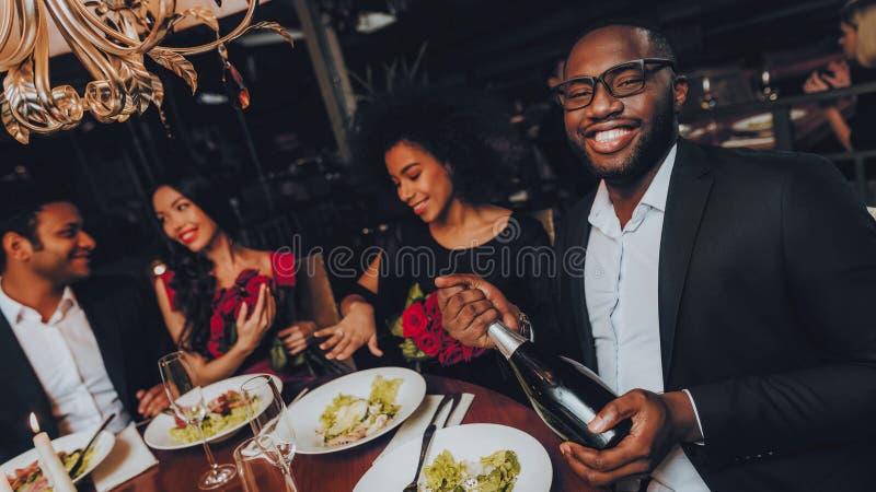 Grupp av lyckliga vänner som möter och har matställen fotografering för bildbyråer