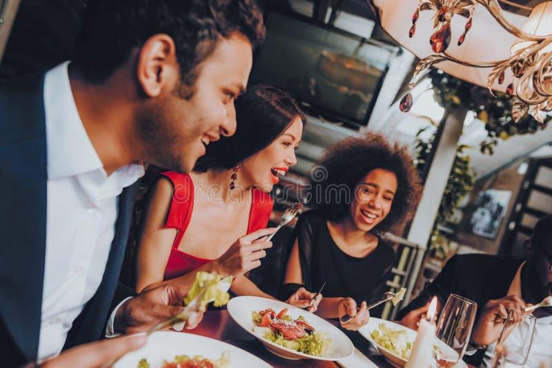 Grupp av lyckliga vänner som möter och har matställen royaltyfri foto