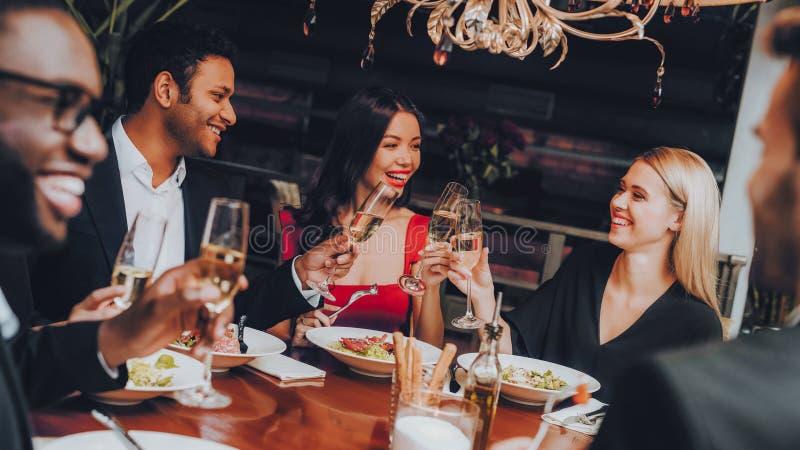 Grupp av lyckliga vänner som möter och har matställen royaltyfri bild