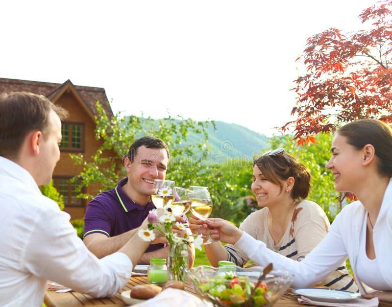 Grupp av lyckliga vänner som rostar vinexponeringsglas i trädgården royaltyfri fotografi