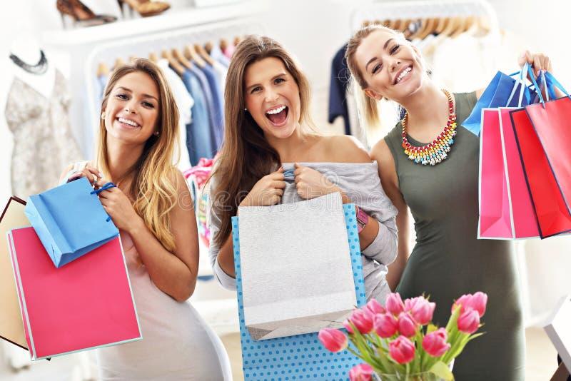 Grupp av lyckliga vänner som shoppar i lager royaltyfria foton