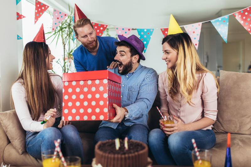 Grupp av lyckliga v?nner som hemma firar f?delsedag och har gyckel fotografering för bildbyråer