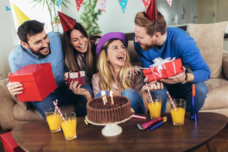Grupp av lyckliga v?nner som hemma firar f?delsedag och har gyckel arkivfoto