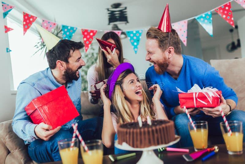 Grupp av lyckliga v?nner som hemma firar f?delsedag och har gyckel arkivbild