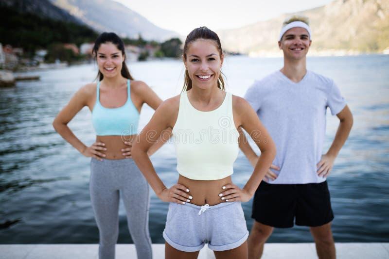 Grupp av lyckligt öva för folk som är utomhus- Sport, kondition, kamratskap och sunt livsstilbegrepp arkivbilder