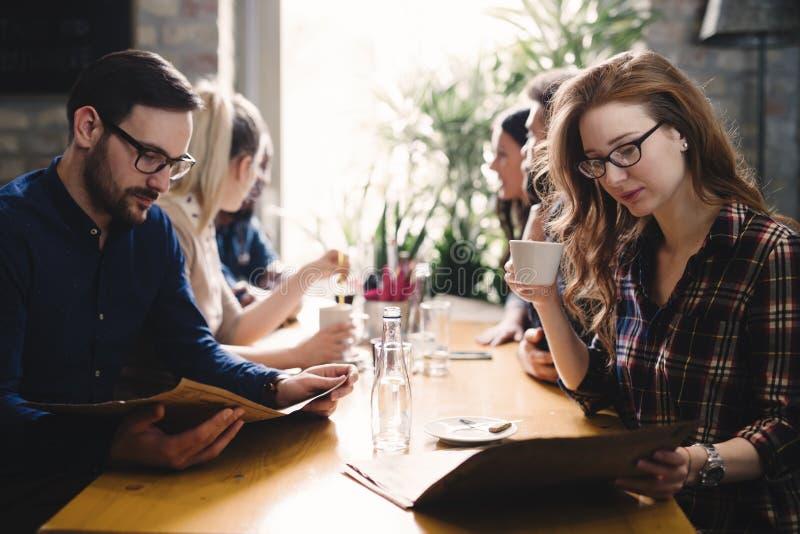 Grupp av lyckligt affärsfolk som äter i restaurang arkivbild