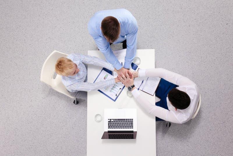 Grupp av lyckligt affärsfolk som tillsammans rymmer händer, medan sitta runt om skrivbordet arkivfoton