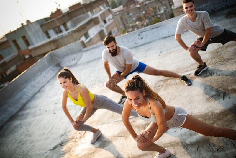 Grupp av lyckligt färdigt öva för vänner som är utomhus- i stad arkivfoton