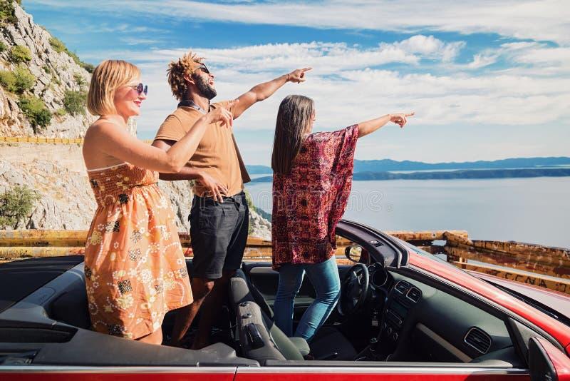 Grupp av lyckligt folk i röd konvertibel bil royaltyfri fotografi